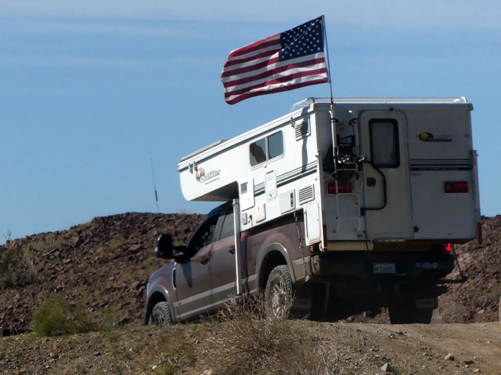 US flag flies over truck camper