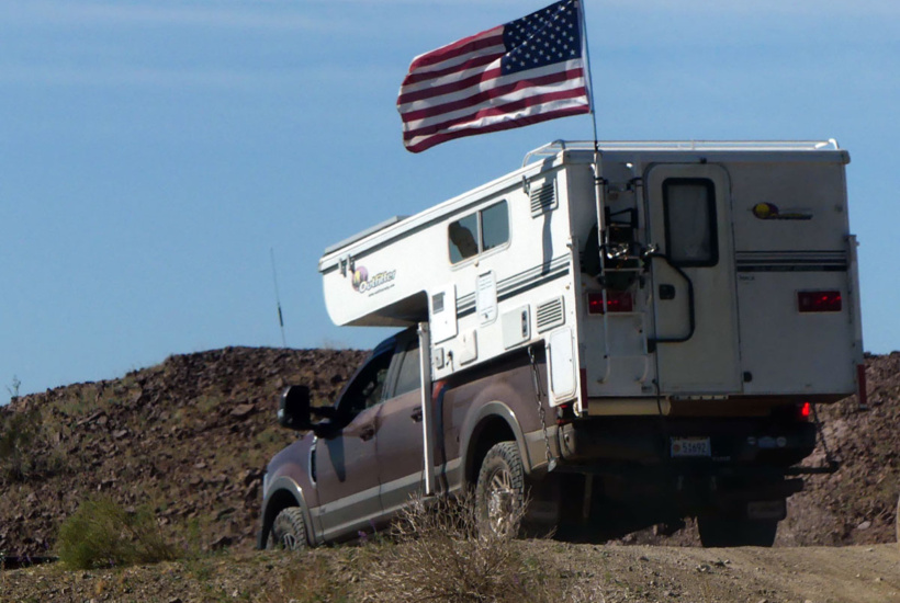 US flag flies over truck camper